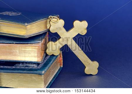 Religious items: old golden cross and ancient books (Holy Bibles) against blue background