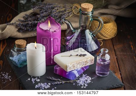 Lavender sea salt, natural organic soaps, lavender oil for spa massage and candle on a dark wooden table
