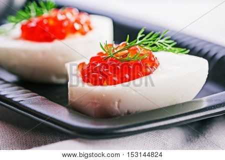 Hard-boiled egg with salted salmon roe filling on dark ceramic plate