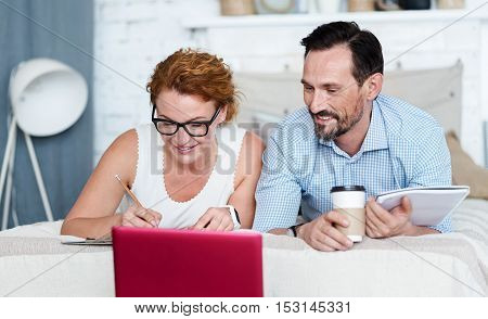 Work with comfort. Nice smiling woman taking some notes and looking at laptop together with her husband holding coffee while lying on bed.