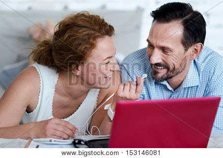 Take them. Close up of vivacious woman giving earphones to bearded man while lying on bed near laptop.