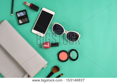 Fashion woman essentials cosmetics cellphone makeup accessories isolated on colorful background Top view