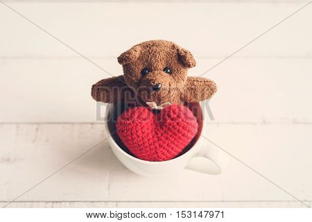 Teddy bear with red heart shape in cup of coffee isolated on white wooden background Vintage tone