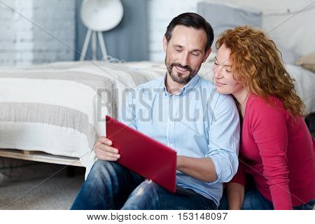 Nice picture. Handsome bearded man holding laptop and showing something to his wife while sitting on floor.