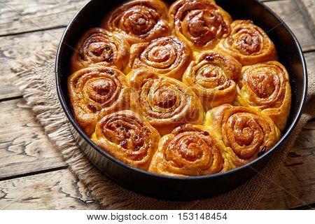 Pumpkin cinnamon dough bun rolls homemade baked sweet autumn dessert swirl bread food on vintage wooden table background