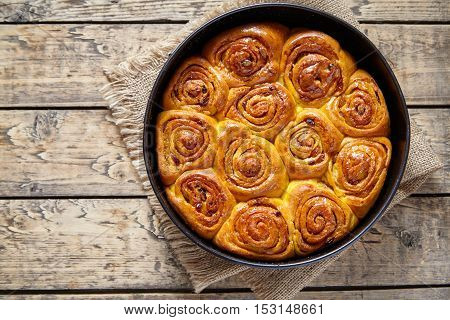 Pumpkin cinnamon dough bun rolls homemade baked sweet autumn holiday dessert swirl bread food on vintage wooden table background