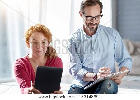 For instagram. Pretty ginger woman taking selfie using tablet while sitting near her husband making notes.