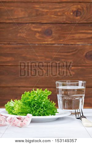 Diet concept. Fresh salat, water and measurement tape - diet and healthy eating concept. On a wooden background