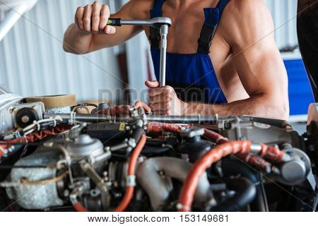 Cropped image of a repair man hands fixing engine on a plane
