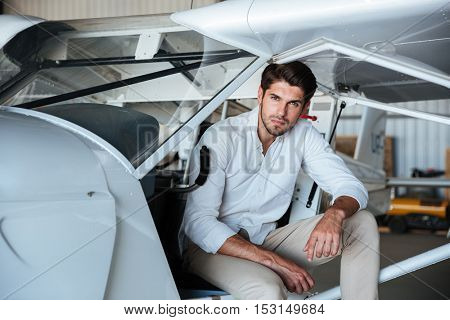 Handsome young man pilot sitting in small airplane