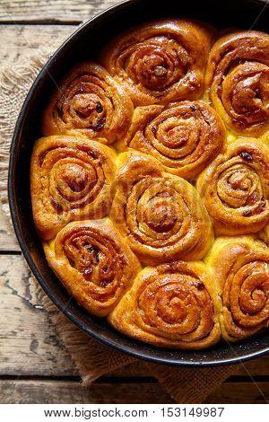 Pumpkin cinnamon dough bun rolls traditional baked vegan sweet autumn cake holiday dessert swirl bread food on vintage wooden table background
