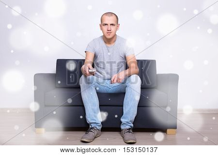 Young Man Sitting On Sofa And Watching Tv At Home