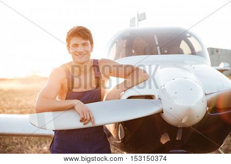 Handsome smiling mechanic in overall standing and looking at camera near airplane landed on the field