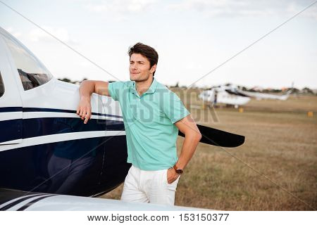 Smiling attractive young man standing near small airlane