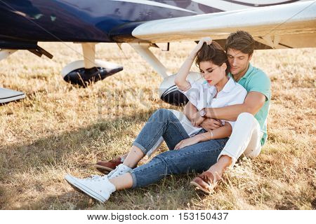 Sensual young couple sitting and embracing near private aircraft