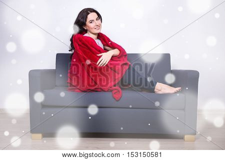 Winter Relaxation Concept - Woman Sitting On Sofa Wrapped In Red Blanket