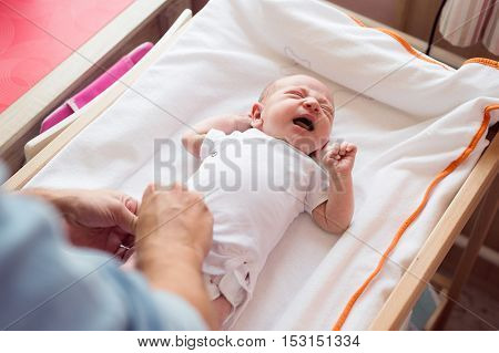 Unrecognizable father changing diaper to his crying baby son lying on nursery table