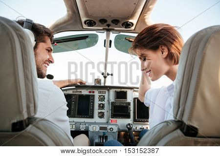 Beautiful young couple looking at each other while sitting inside airplane cabin