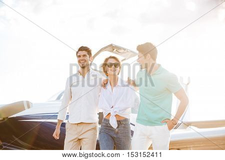 Happy young friends walking on runway in airport and smiling