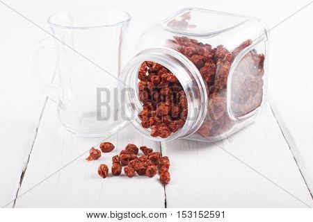 Dried rowan berries in a glass jar on a white table.