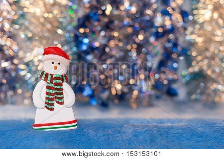 Close-up of a snowman figurine on a colorful background bokeh. New Year or Christmas picture.