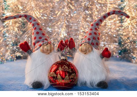Two cheerful gnomes with  hands up in red mittens and high caps holding red glass Christmas ball on silver bokeh background. Christmas or New Year picture.