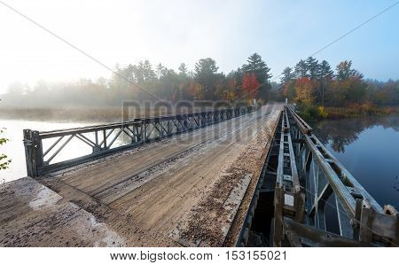 Early October, misty morning sunshine on a portable deployable, single lane, steel and timber bridge over Corry Lake in Chalk River Ontario, Canada.
