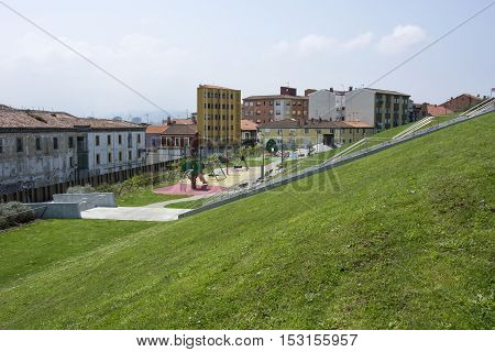 Photo of several buildings with green grass, several colours and sunlight