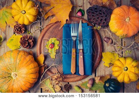 Thanksgiving dinner background with round board. Autumn pumpkin and fall leaves on wooden table. View from above