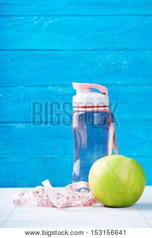 Fitness concept with water, measurement tape and fresh apple on a blue background