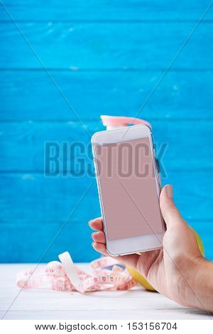 Women takes photo with smarphone with empty screen. Water and measurement tape - diet and sport eating concept. On a wooden background. Shooting for social media