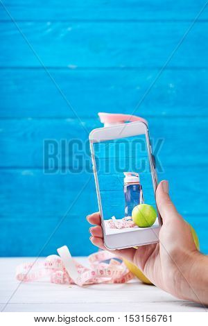 Women takes photo with smarphone fitness concept on a screen. Fresh apple, water and measurement tape - diet and sport eating concept. On a wooden background. Shooting for social media