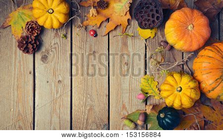Thanksgiving dinner background. Autumn pumpkin and fall leaves on wooden table. View from above