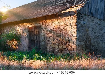 Closed wooden door in a stone wall of an old barn.