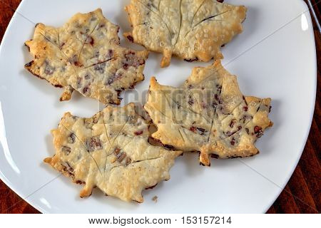 Chocolate cookies cut in the shape of a leaf with nuts