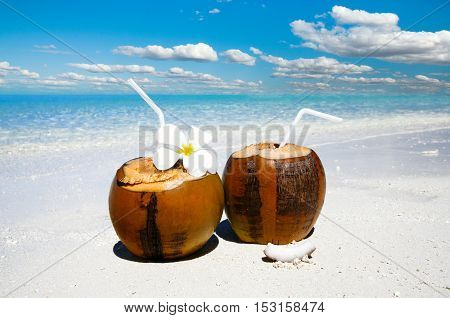 Two coconut cocktails on white sand beach next to clean sea blue water. Vacation and travel concept