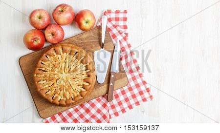 Homemade apple pie topped with slices of apples and cinnamon on white wooden table. Nearby are five red apples knife checkered napkin and cake shovel. Top view. Copyspace.