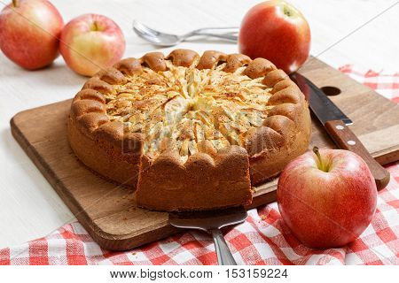 Homemade apple pie topped with slices of apples and cinnamon on white wooden table. Nearby are red apples and knife on checkered napkin.