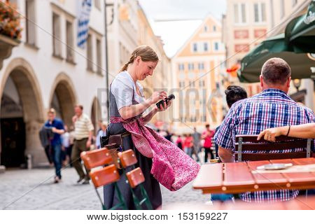 Munich, Germany - July 03, 2016: Bavarian waitress in thraditional clothes taking order outdoors at the pub in Munich