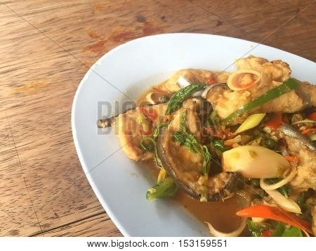 horizontal photo of fried spicy Mekong giant catfish with herb on wooden background copyspace