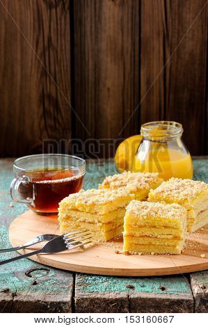 Homemade tasty layered lemon cake with tea and lemon curd on shabby wooden background with copyspace