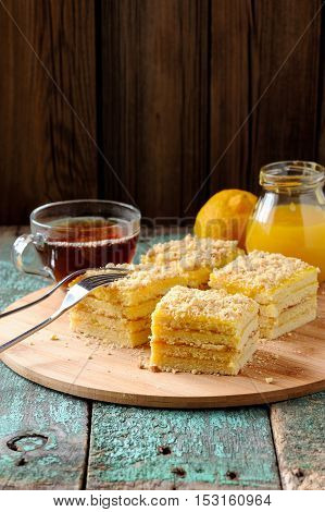 Tasty square layered lemon cake with black tea and lemon curd on shabby wooden background vertical