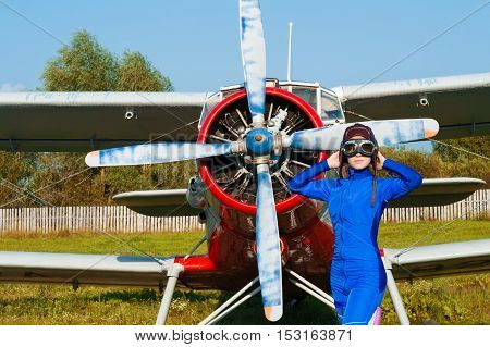woman pilot in helmet standing with airplane outdoors