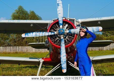 attractive pilot in helmet standing with airplane
