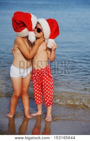 two children in Christmas hats kissing in the background of the sea. Winter holidays in hot countries