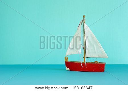 Vintage wood red sailboat resting on blue waters with blue background