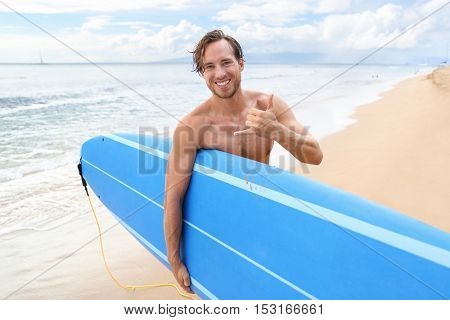 Surfer guy happy with surf surfing smiling doing hawaiian shaka hand sign for fun during surf session in ocean waves on beach vacation. Surfing travel destination. Friendly greeting in surfer culture.