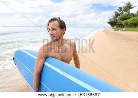Surfer man carrying longboard surfboard going surfing on Kaanapali beach, Maui. Professional male athlete going for a surf session at hawaiian destination. Travel lifestyle summer travel vacation.