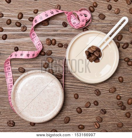 Cellulite busting cosmetic products concept. Anti-cellulite cosmetics with caffeine. Jar of cream with coffee essential oil, natural body scrub, body measuring tape and scattered coffee beans