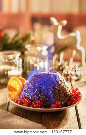 Christmas pudding flambe on wooden table in rustic